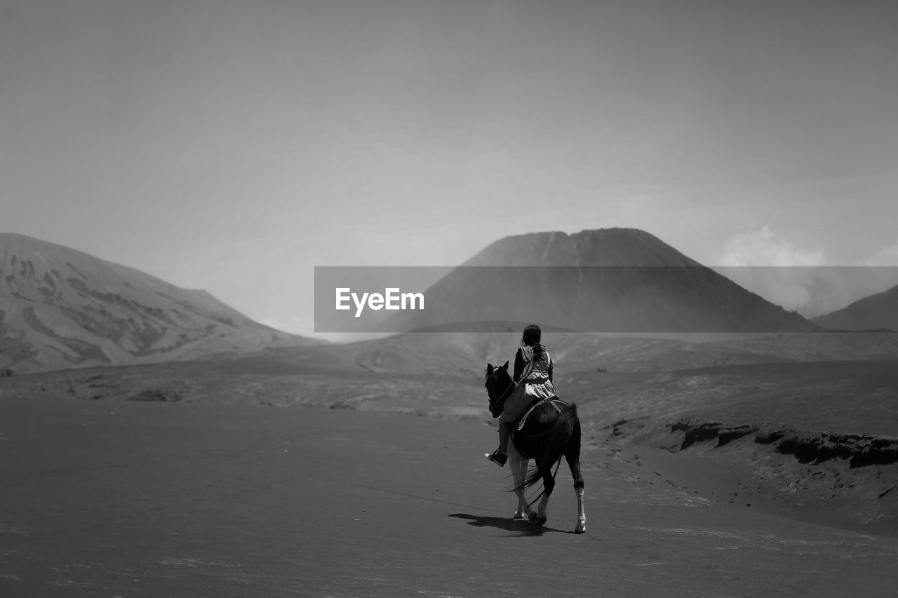 Woman riding horse on sand against mountains