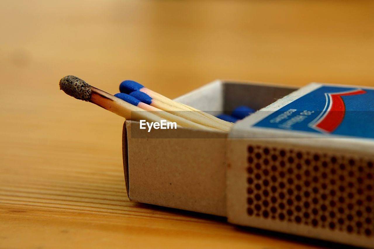 Close-up of sticks in matchbox on table