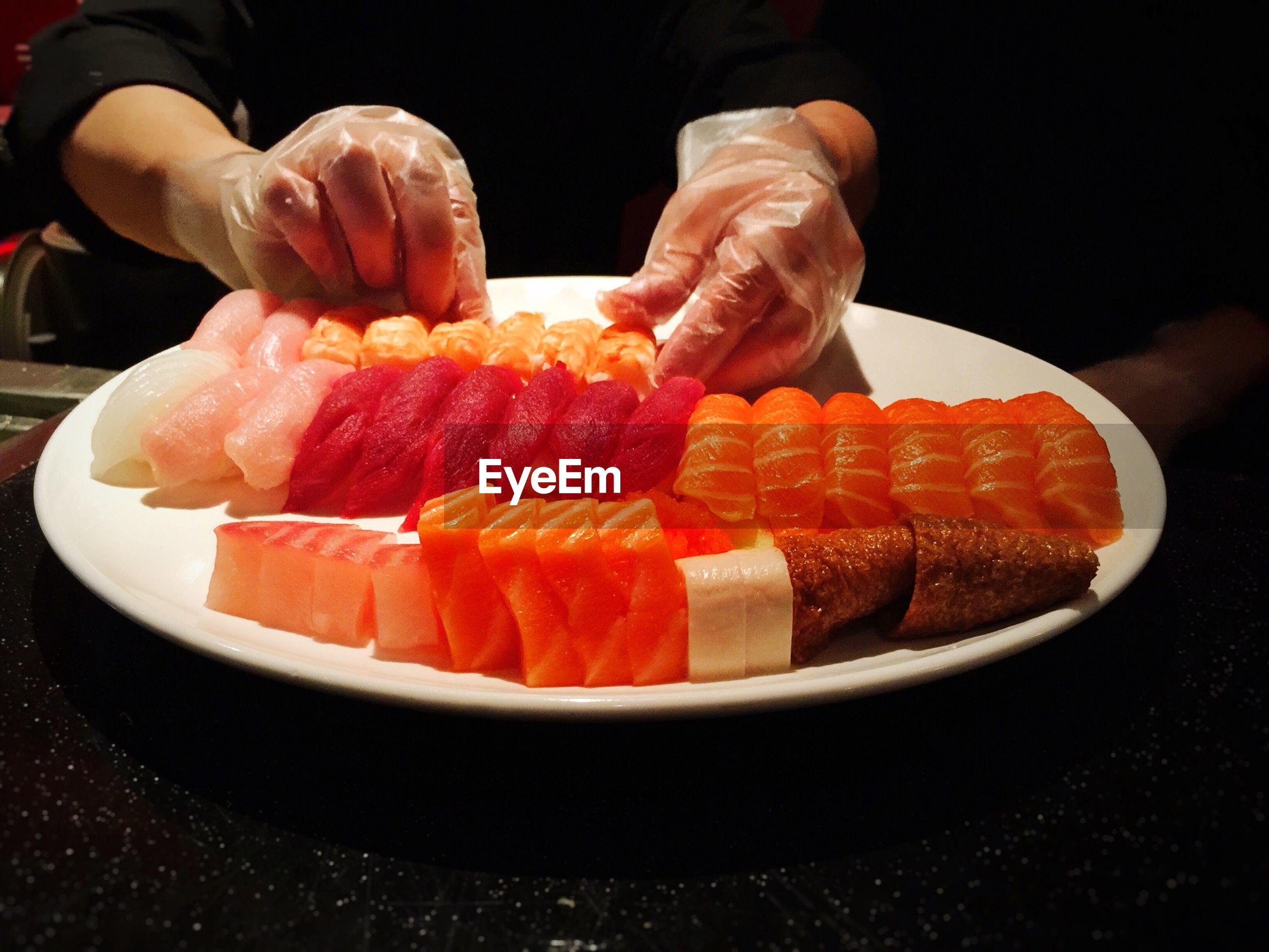 Cropped image of hand arranging salmon sashimi on plate