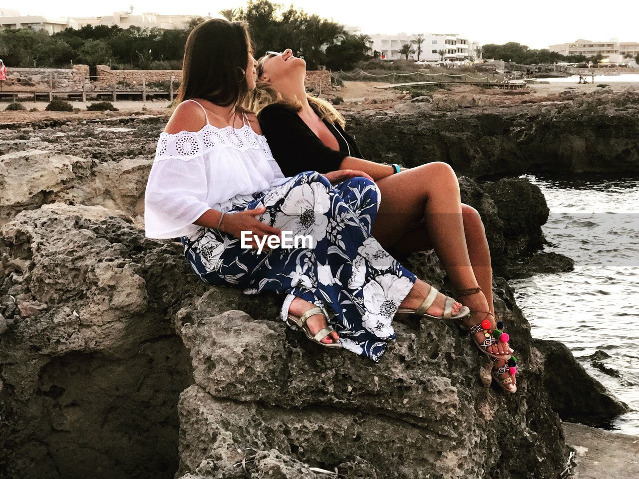 two people, real people, togetherness, rock - object, leisure activity, love, rear view, lifestyles, women, young women, day, young adult, outdoors, bonding, vacations, retaining wall, water, nature, sky, adult, people