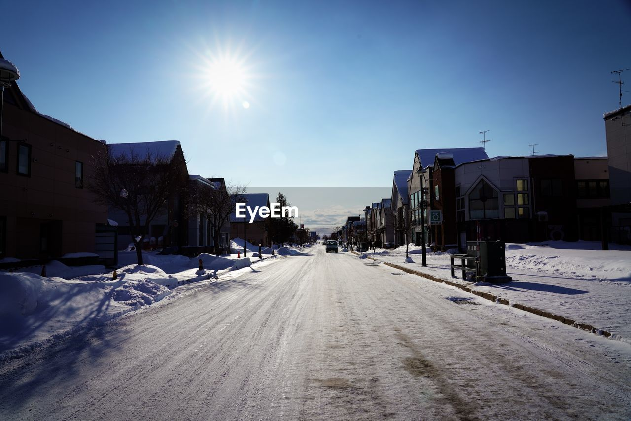 building exterior, architecture, sky, built structure, snow, winter, cold temperature, sunlight, city, transportation, nature, building, direction, road, the way forward, street, sun, covering, day, diminishing perspective, lens flare, no people, outdoors, bright