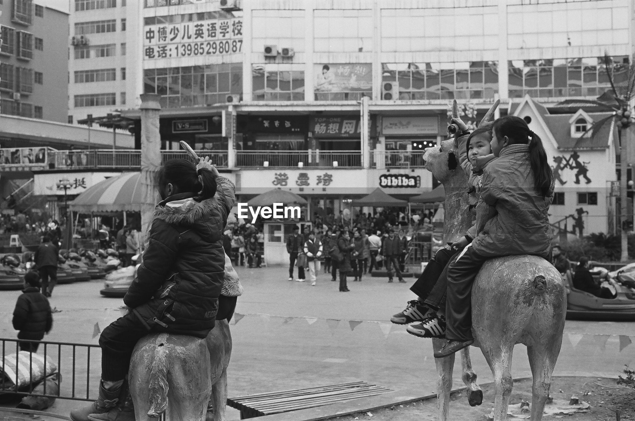 PEOPLE SITTING ON STREET AGAINST BUILDINGS