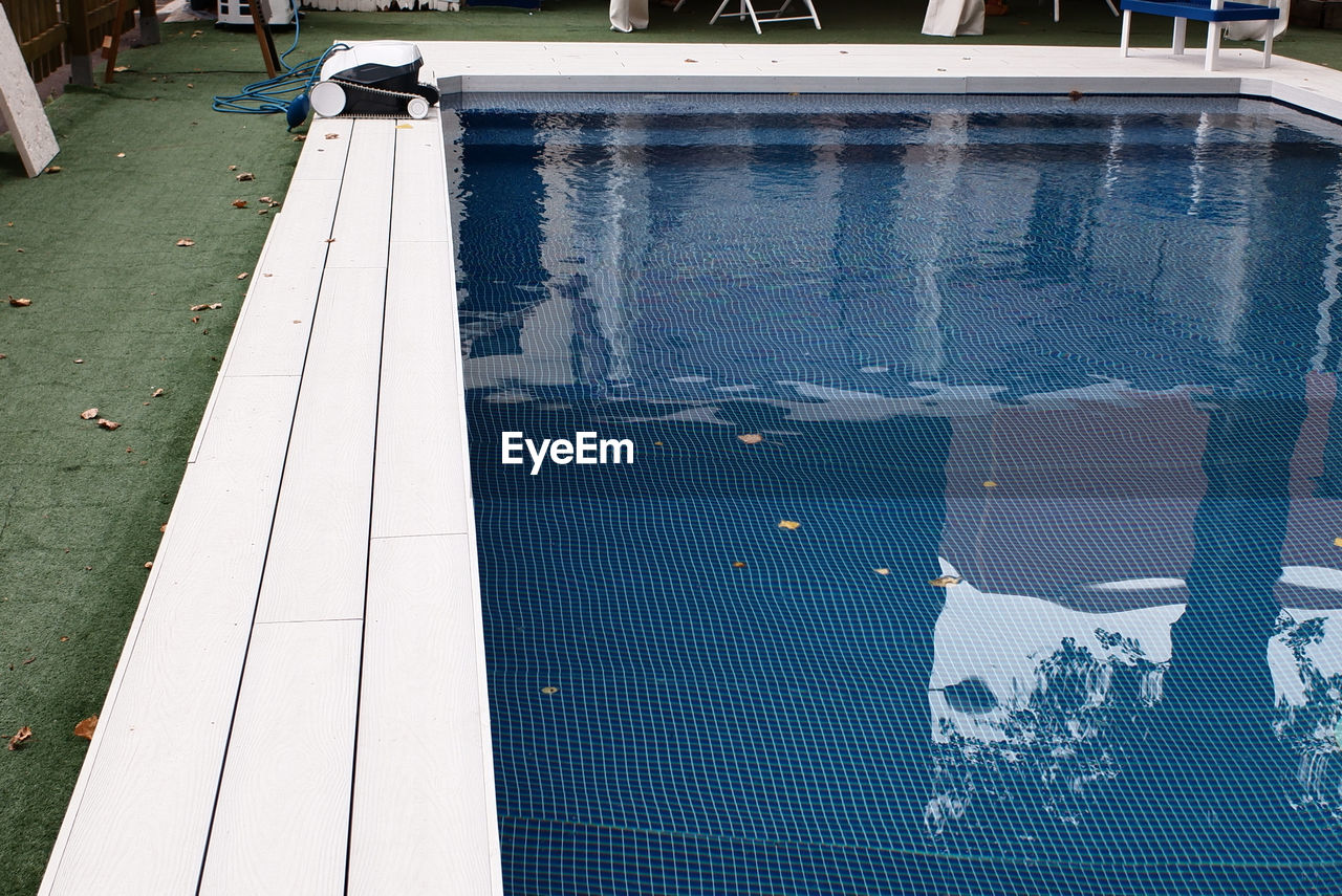 HIGH ANGLE VIEW OF PEOPLE SWIMMING POOL