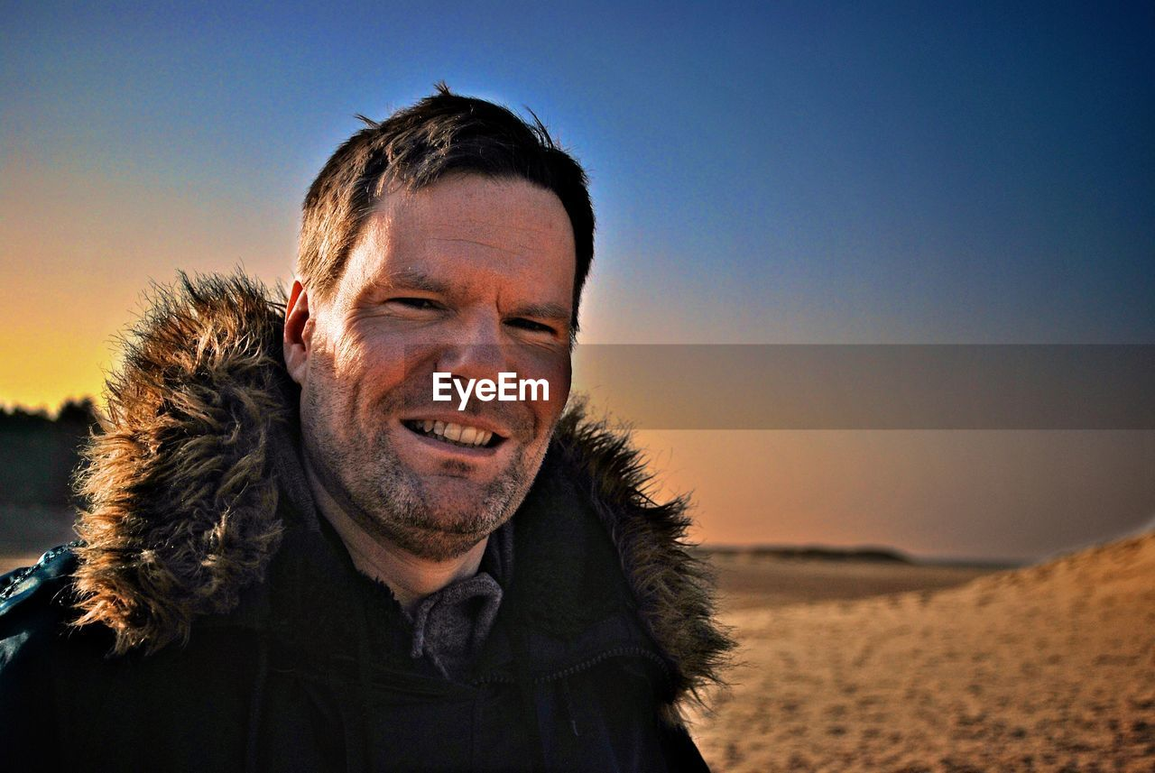 real people, outdoors, mature men, nature, one person, sky, portrait, lifestyles, mature adult, happiness, leisure activity, smiling, looking at camera, front view, clear sky, focus on foreground, headshot, beard, beauty in nature, sunset, beach, sand, vacations, men, day, close-up