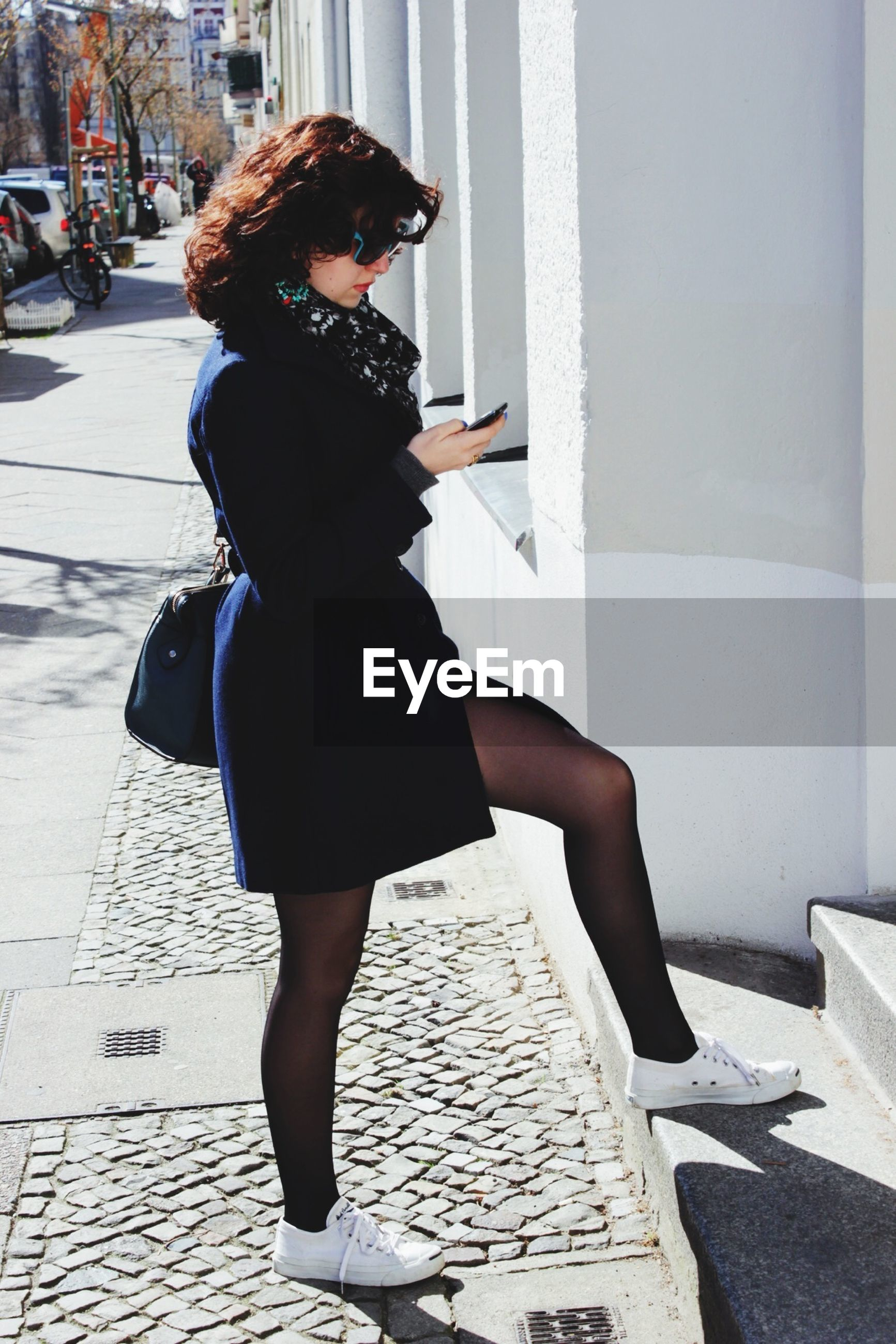 Full length of beautiful woman using phone on sidewalk in city