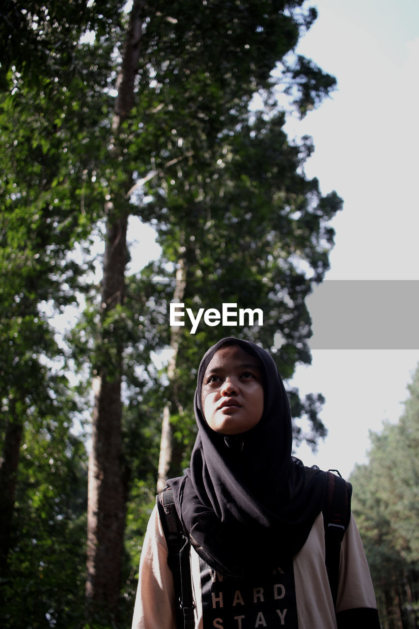 Low Angle View Of Young Woman In Hijab Standing Against Trees