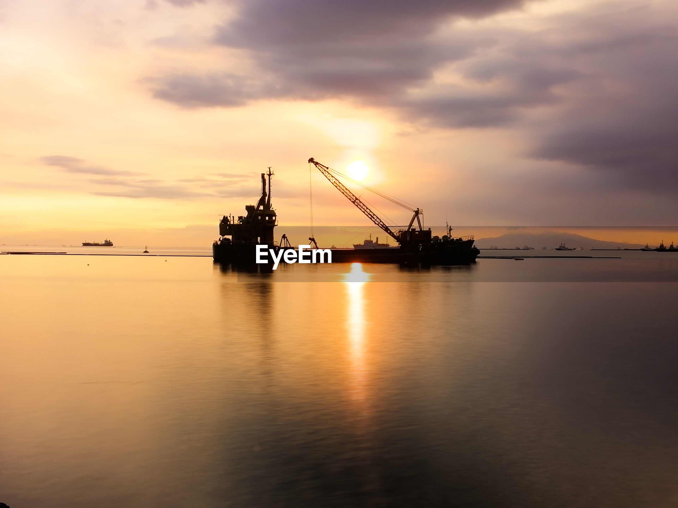SILHOUETTE OF CRANES AT COMMERCIAL DOCK AGAINST SKY DURING SUNSET