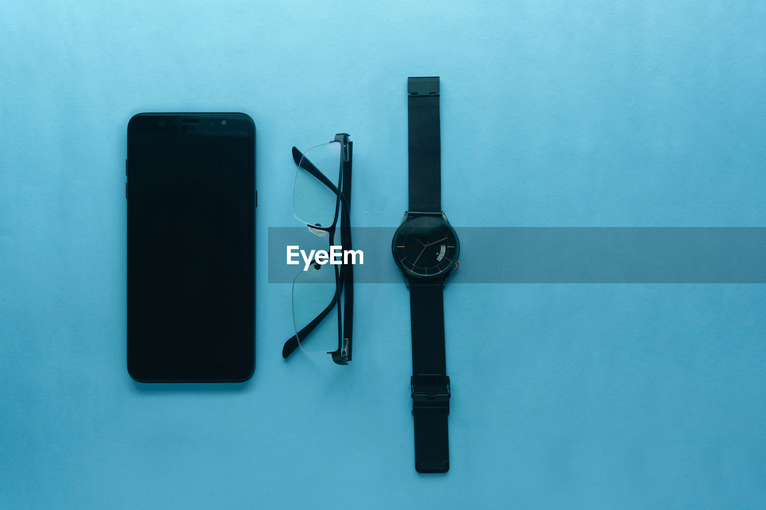 High angle view of gadget, eye-glasses and watch on table against blue background