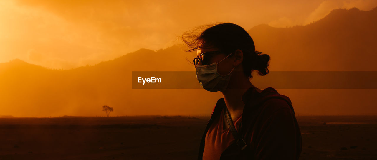 Woman wearing face mask standing against orange sky at sunset