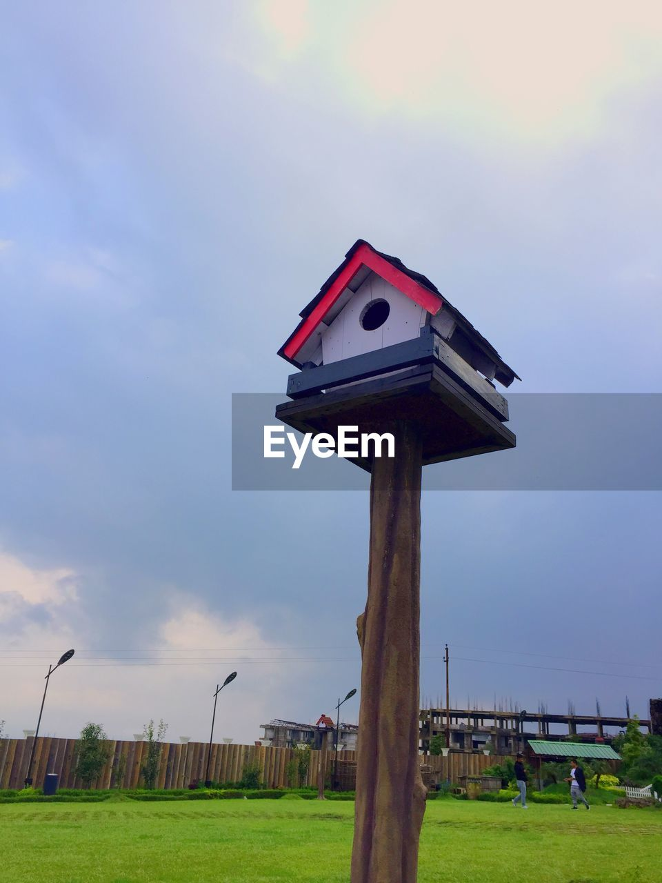 sky, grass, cloud - sky, nature, plant, day, architecture, no people, built structure, green color, outdoors, field, land, red, birdhouse, wood - material, building exterior, low angle view, security, protection, wooden post