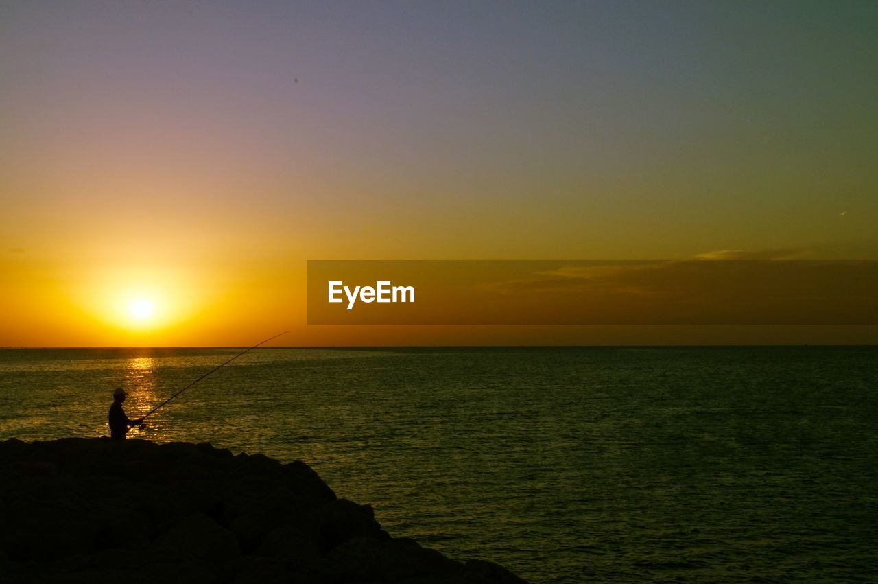 Man Fishing By Sea Against Orange Sky