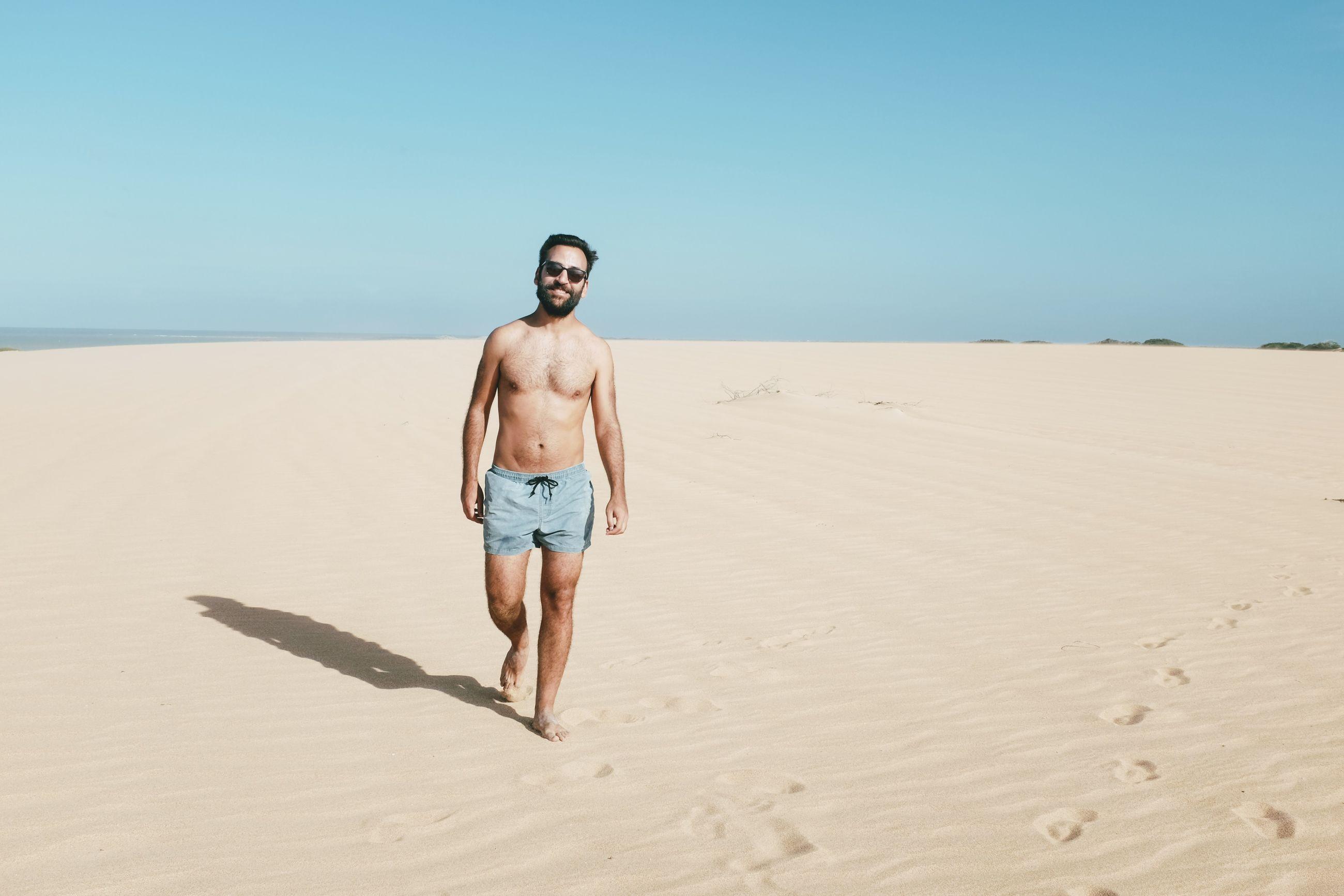 Full length of shirtless man walking on sand at beach