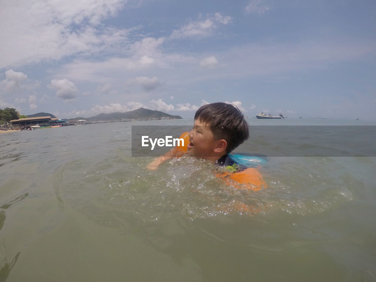 Boy swimming in sea against sky