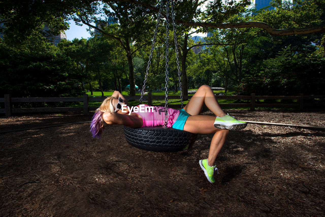 Side view full length of woman relaxing on swing at park