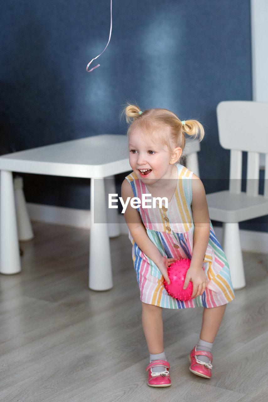 Full length of smiling girl at home