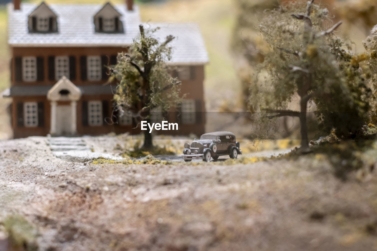 selective focus, built structure, building exterior, architecture, building, transportation, motor vehicle, car, tree, house, mode of transportation, nature, plant, day, outdoors, residential district, land vehicle, no people, city, field, small