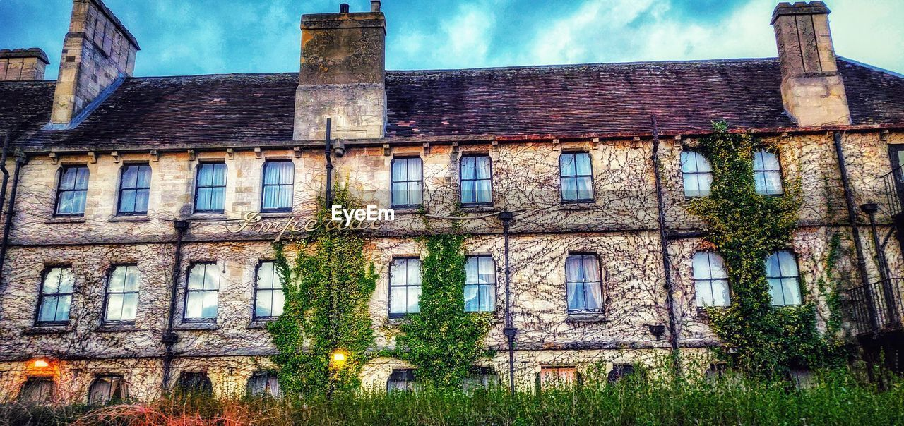 architecture, built structure, building exterior, building, window, abandoned, old, low angle view, sky, history, no people, nature, plant, the past, cloud - sky, day, residential district, ivy, outdoors, weathered, deterioration, ruined