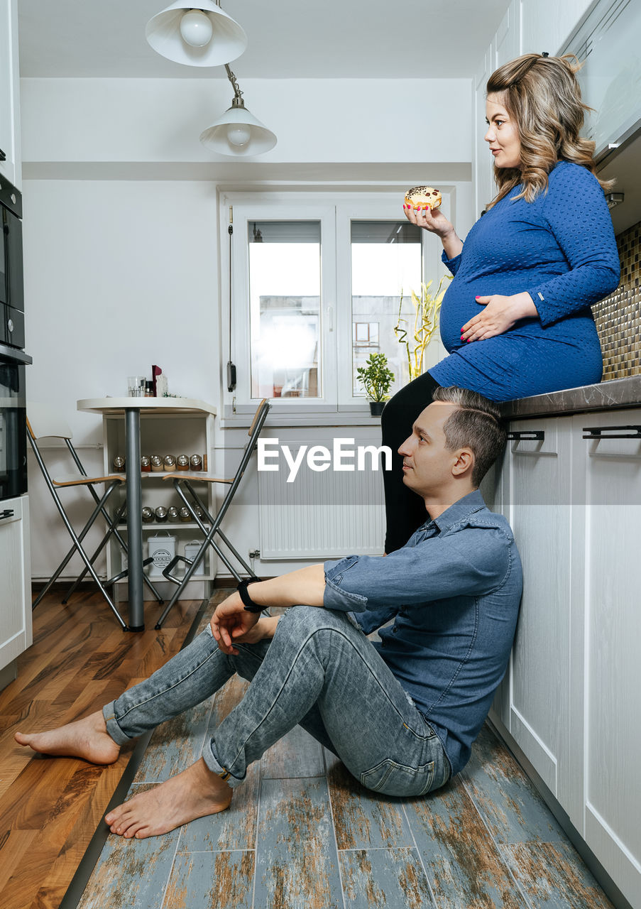 Man With Pregnant Woman Sitting At Home