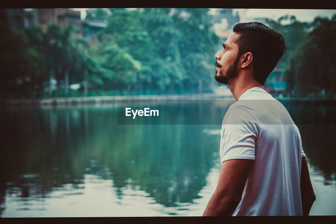 water, one person, real people, side view, young men, lake, lifestyles, standing, looking, focus on foreground, casual clothing, waist up, men, young adult, day, nature, leisure activity, looking away, outdoors, contemplation, profile view