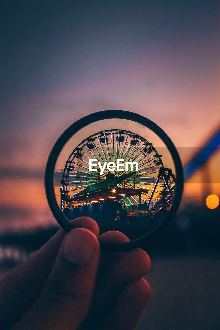 Cropped Hand Holding Lens Against Ferris Wheel During Sunset