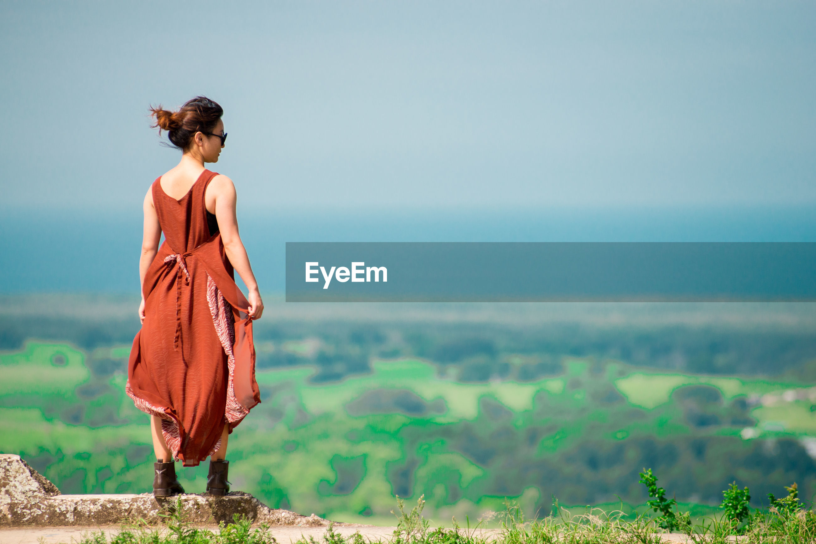 Rear view of young woman looking at sea while standing on observation point against sky