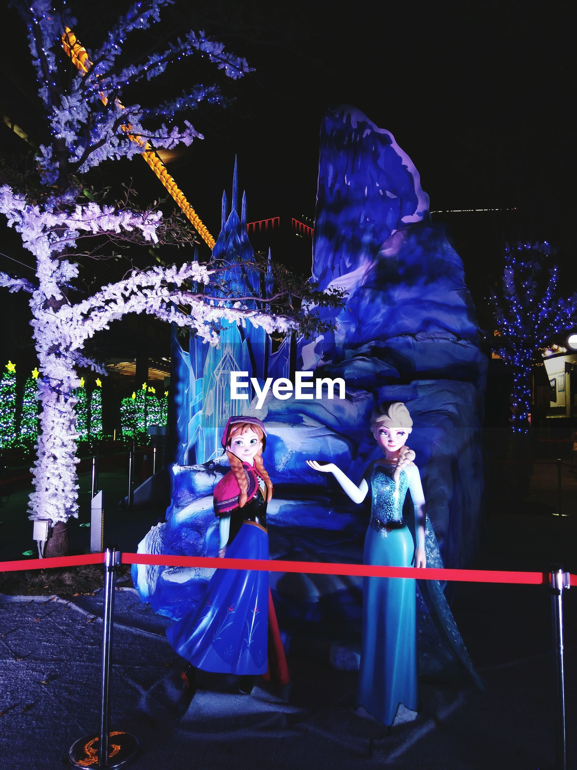 night, illuminated, real people, arts culture and entertainment, lifestyles, costume, celebration, leisure activity, two people, carnival, long exposure, nightlife, standing, architecture, sculpture, outdoors, women, young women, full length, building exterior, city, young adult, carousel, people