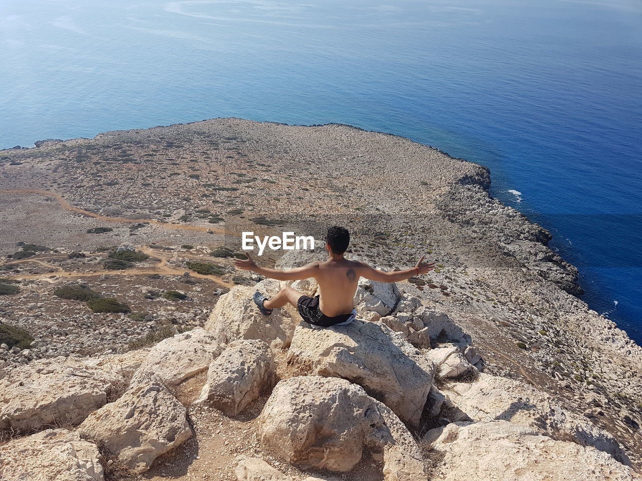 High angle view of man sitting on rock at beach