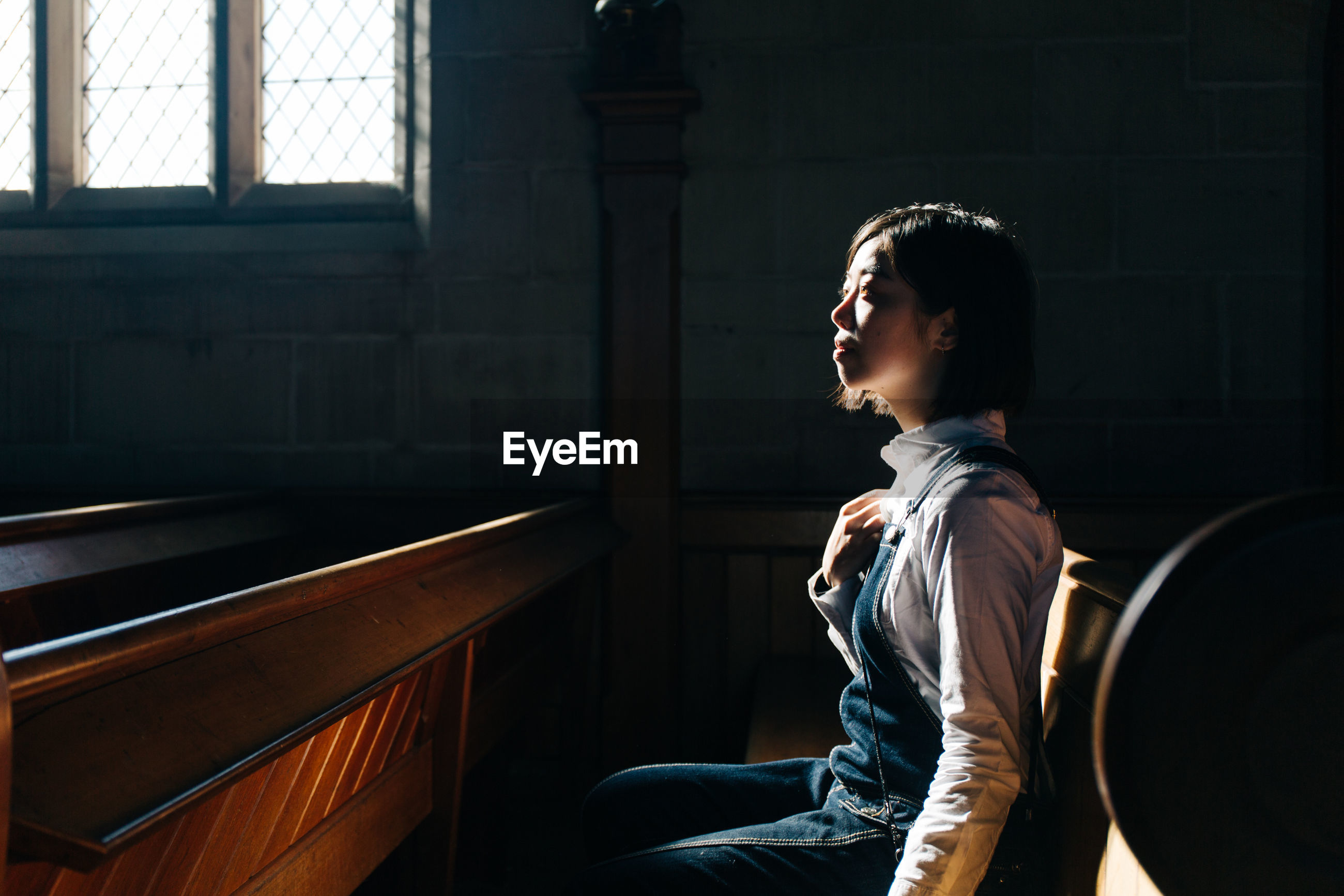 Side view of woman looking away while sitting in church