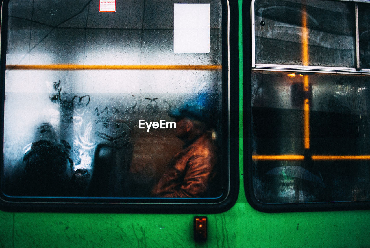 window, real people, mode of transportation, glass - material, one person, men, public transportation, transportation, indoors, transparent, lifestyles, train, train - vehicle, rail transportation, leisure activity, land vehicle, reflection, day, occupation, subway train