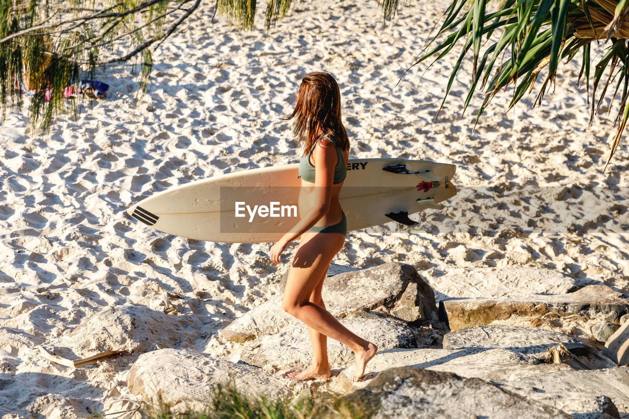 one person, full length, leisure activity, nature, real people, land, beach, lifestyles, women, day, sunlight, holiday, water, vacations, trip, adult, surfboard, sand, tree, outdoors, hairstyle
