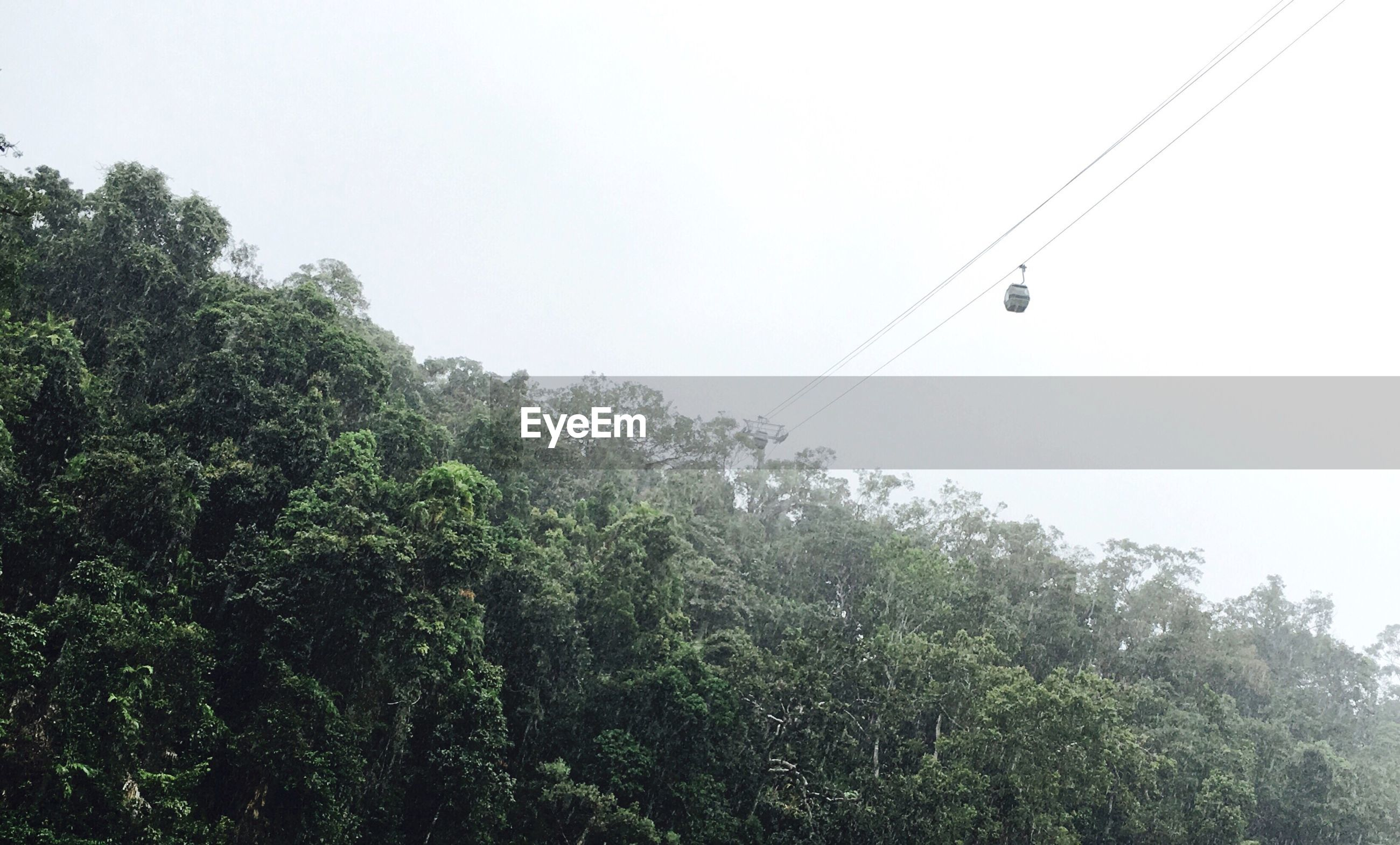 Low angle view of overhead cable car against sky