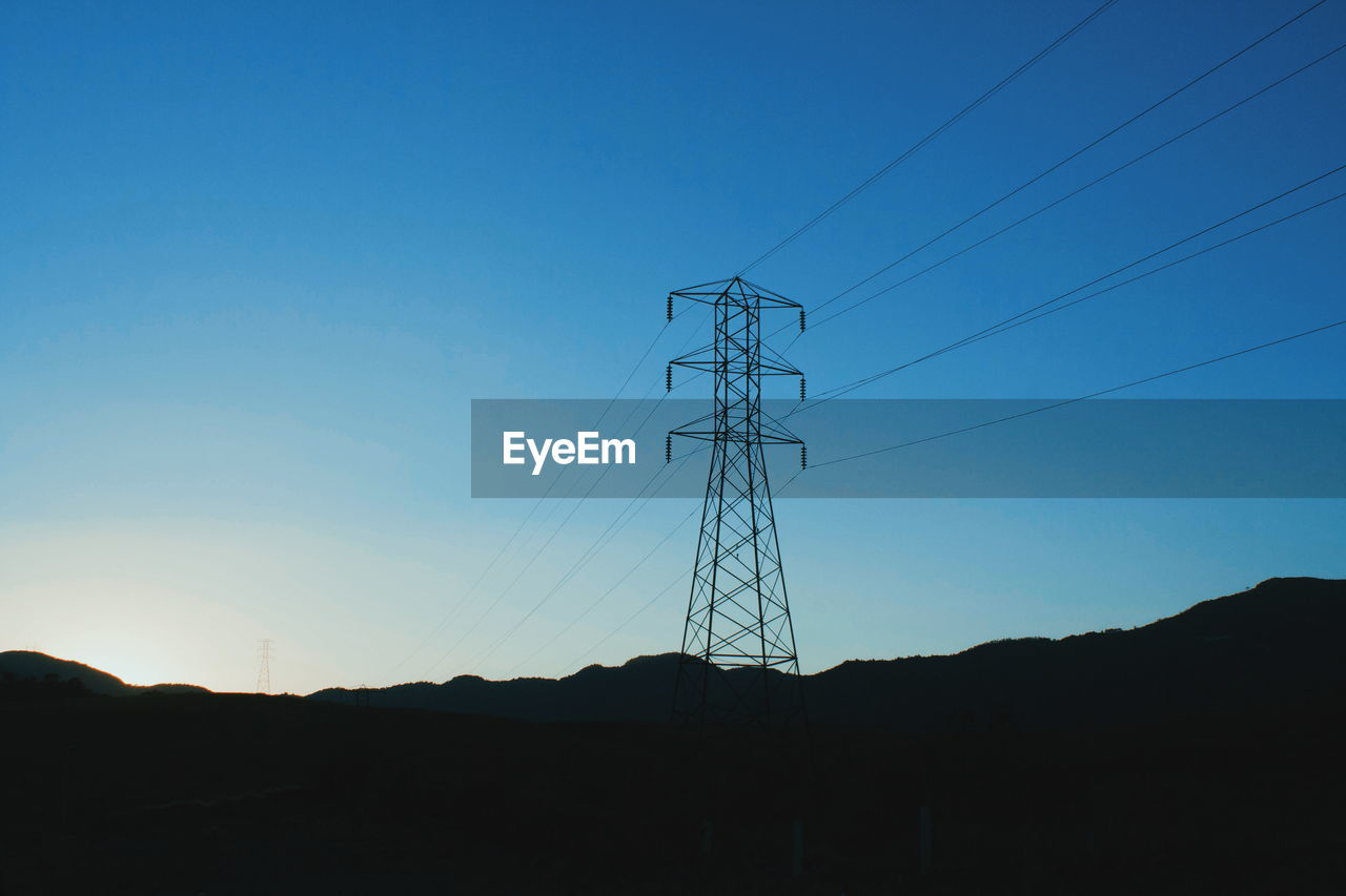 LOW ANGLE VIEW OF SILHOUETTE ELECTRICITY PYLONS ON FIELD AGAINST SKY