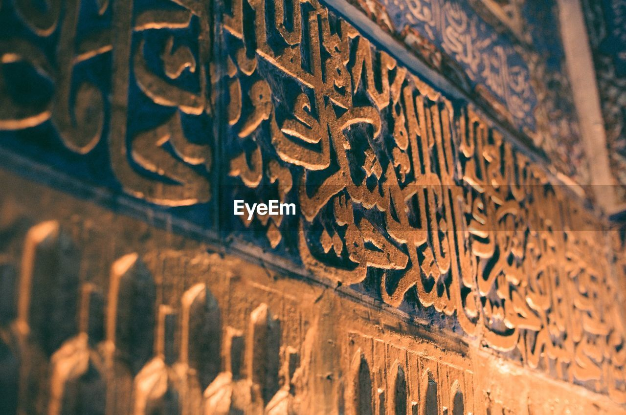 selective focus, spirituality, history, text, indoors, religion, ancient, no people, place of worship, close-up, day, architecture, ancient civilization