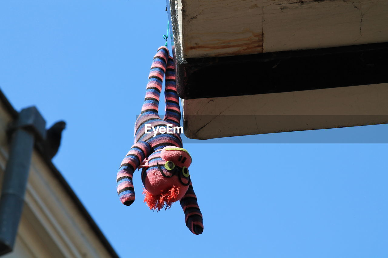 Low Angle View Of Toy Hanging On Building Against Clear Blue Sky