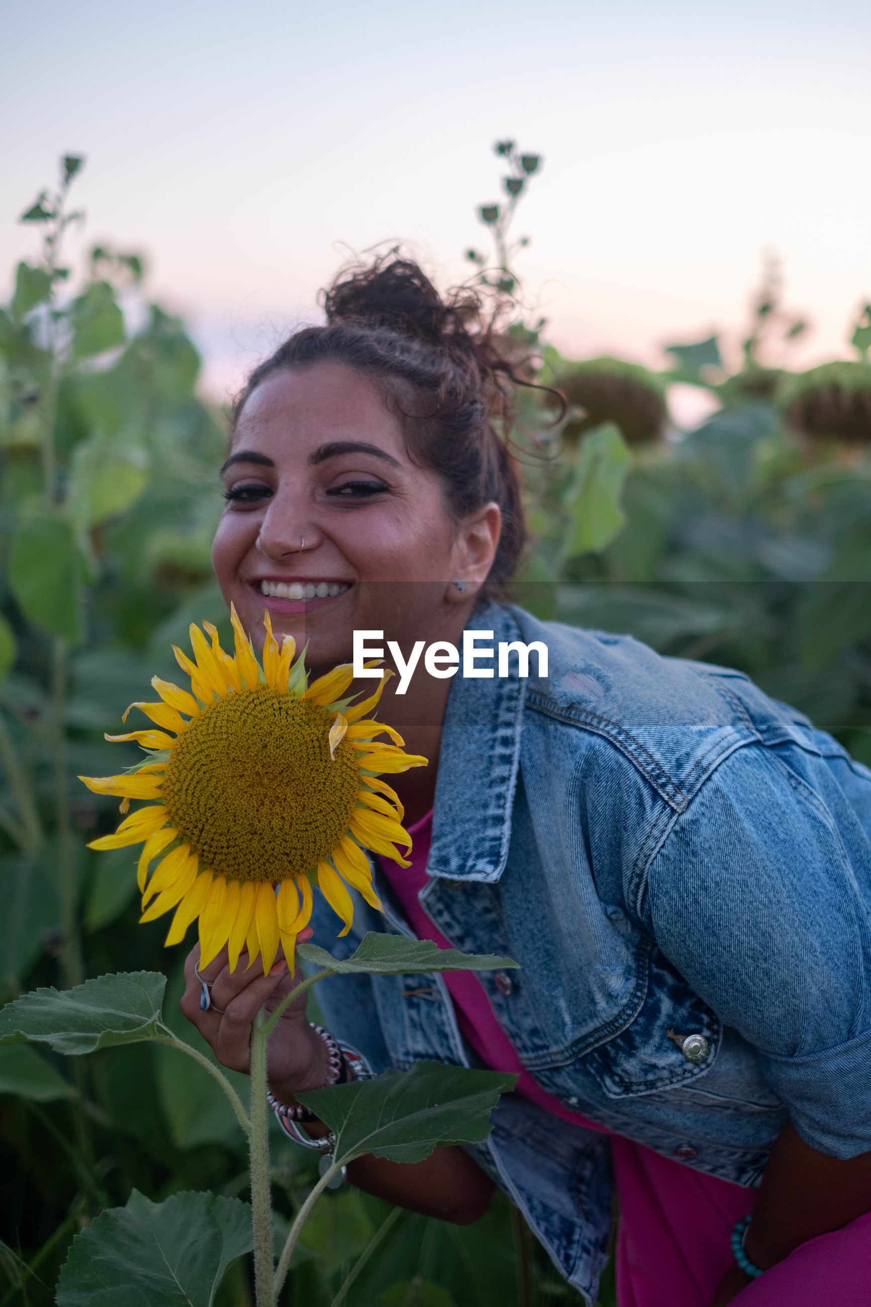 Smiling young woman with sunflower plants