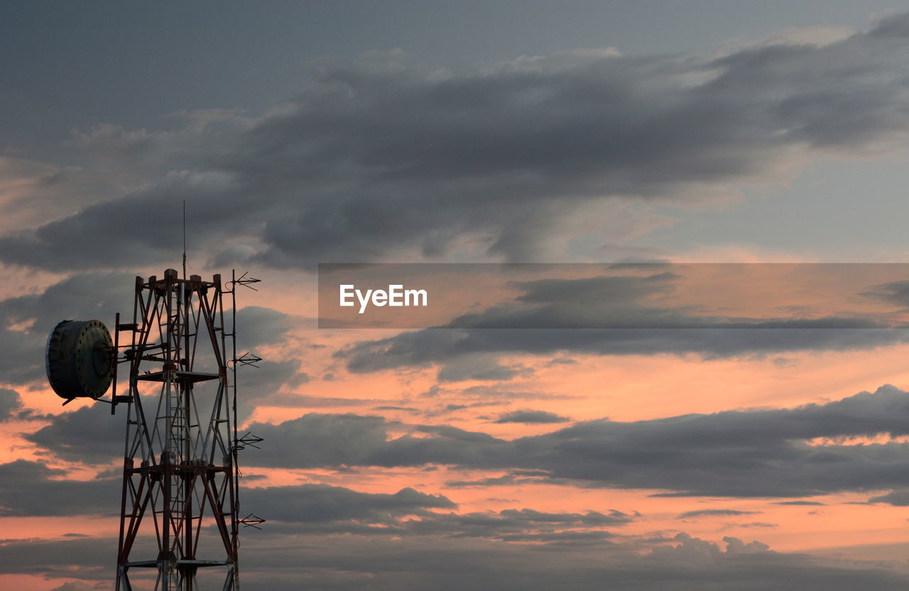 LOW ANGLE VIEW OF COMMUNICATIONS TOWER AGAINST ORANGE SKY