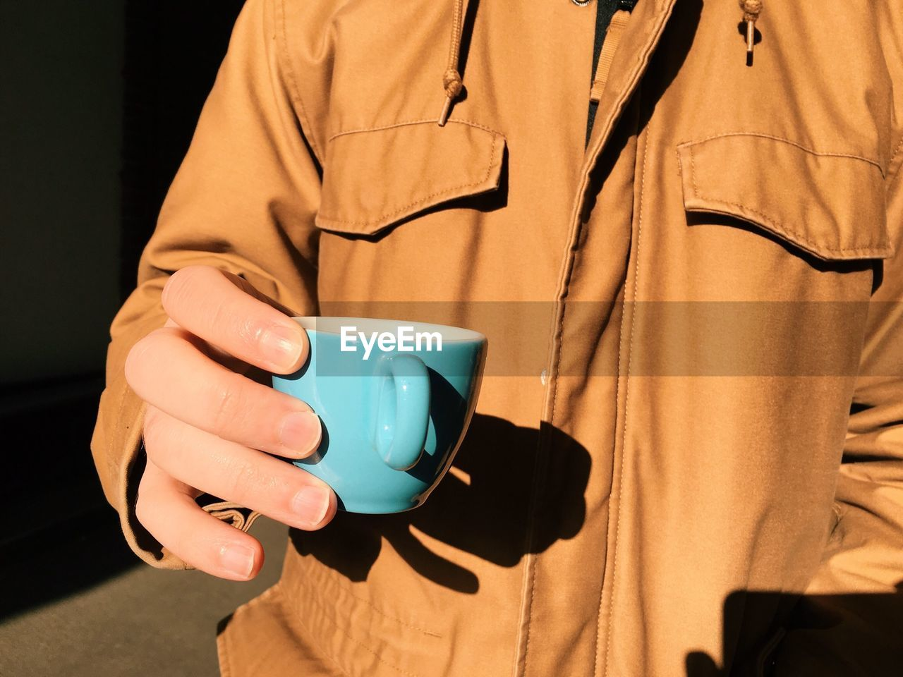 Mid Section View Of Man Holding Cup Of Tea