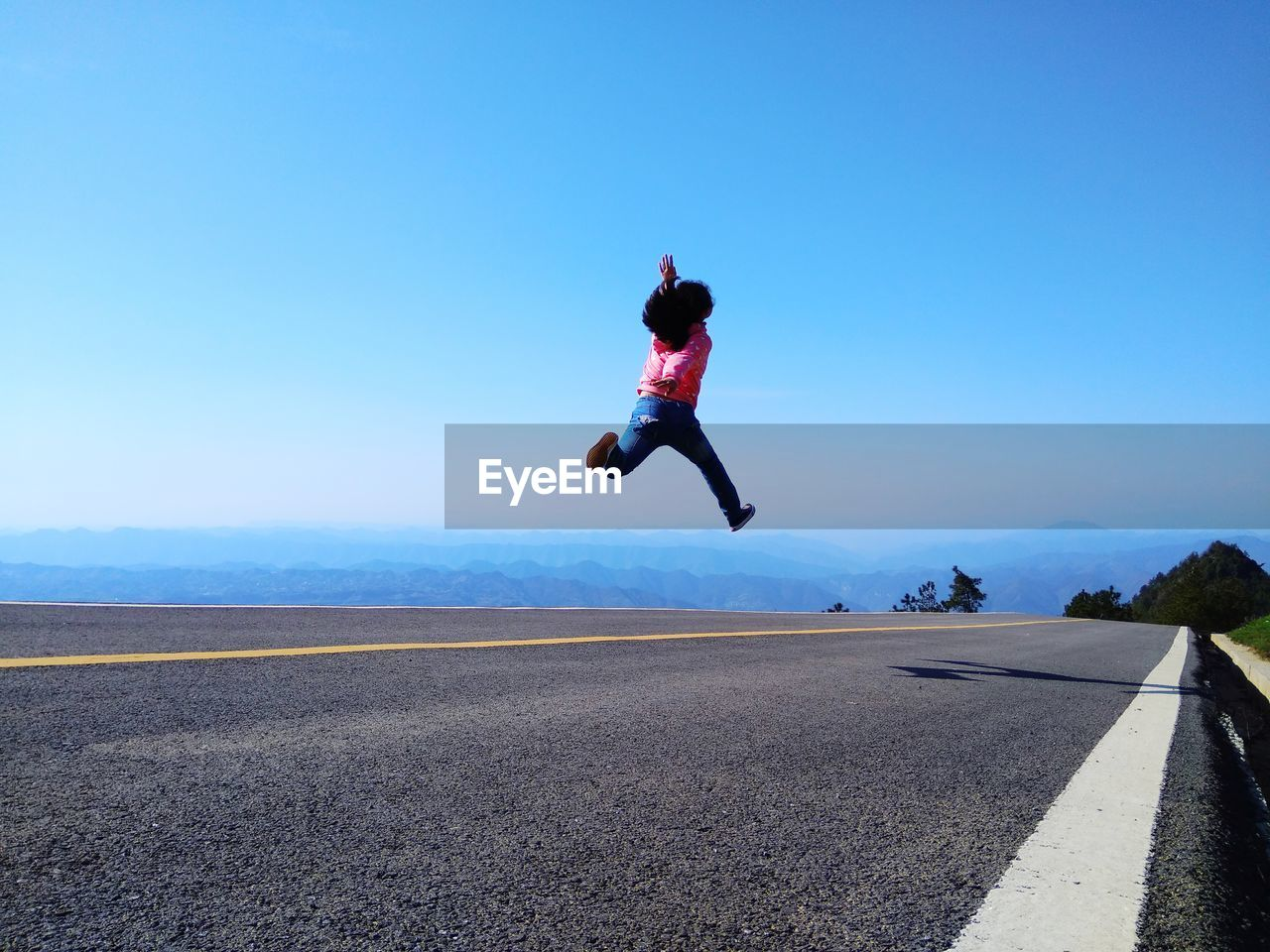Girl Jumping On Road Against Clear Blue Sky