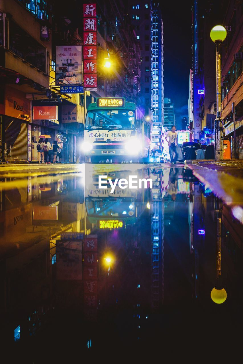 illuminated, night, building exterior, city, architecture, built structure, reflection, no people, building, glowing, street, communication, city life, text, multi colored, light - natural phenomenon, city street, transportation, lighting equipment, advertisement, office building exterior, light, skyscraper