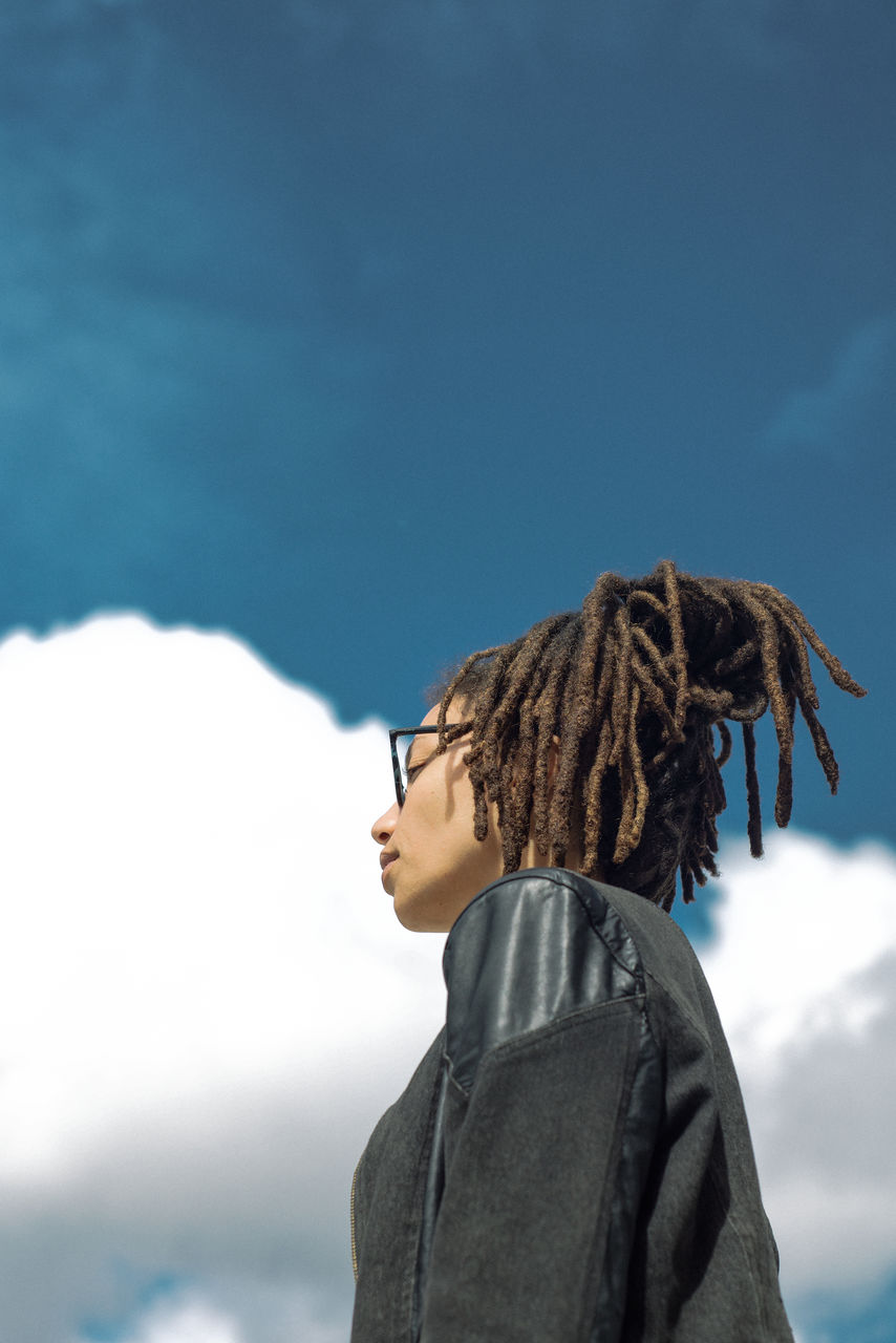 Low Angle View Of Young Woman With Dreadlocks Standing Against Cloudy Sky During Sunny Day