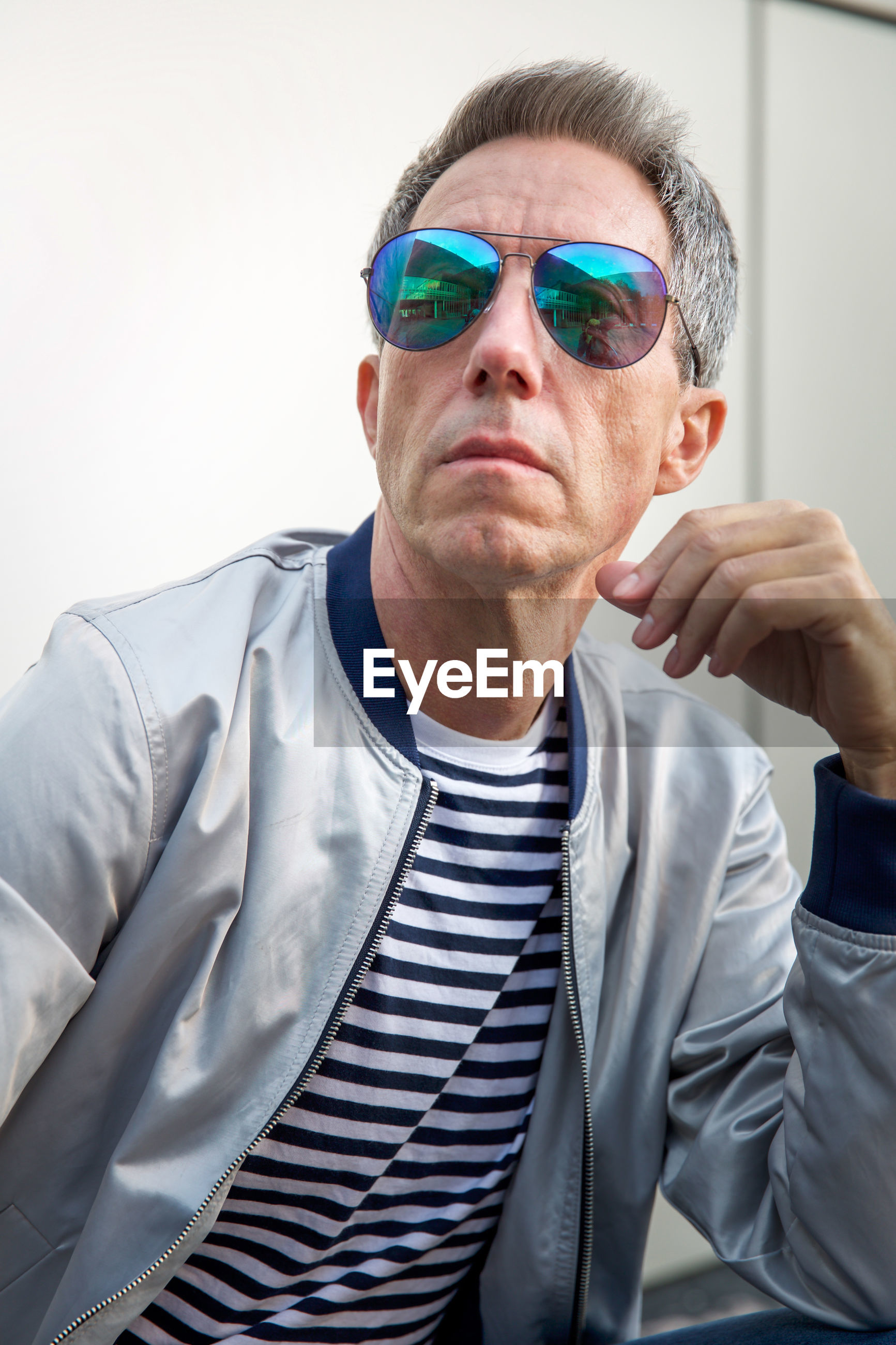 Man wearing sunglasses sitting against wall