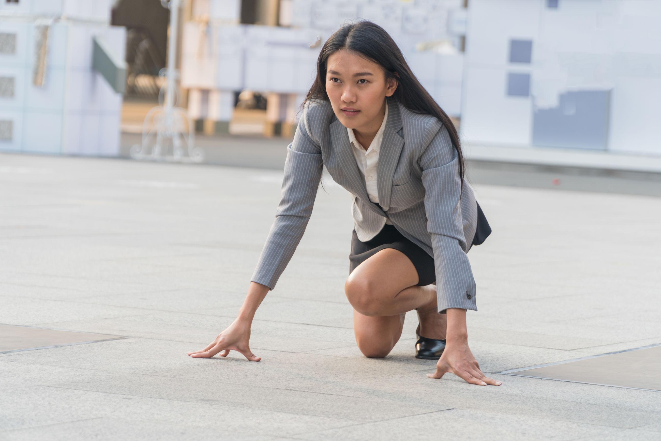 Full length of businesswoman kneeling on city street
