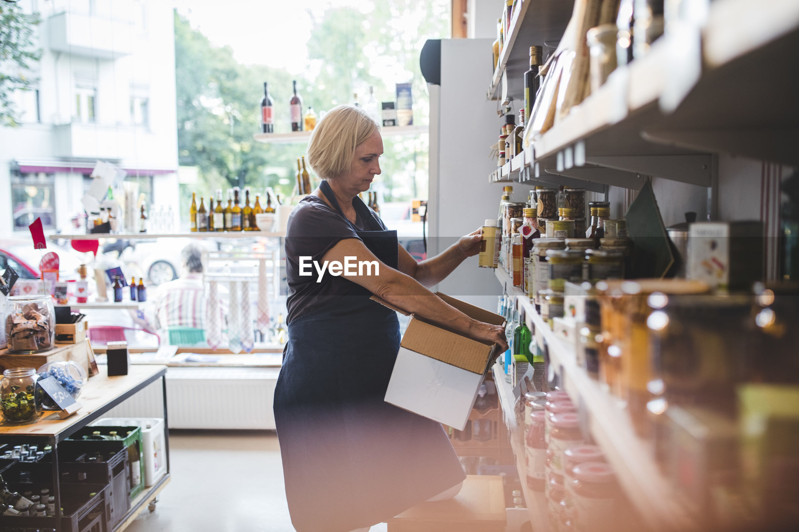 Mature female employee arranging food products on shelf in deli
