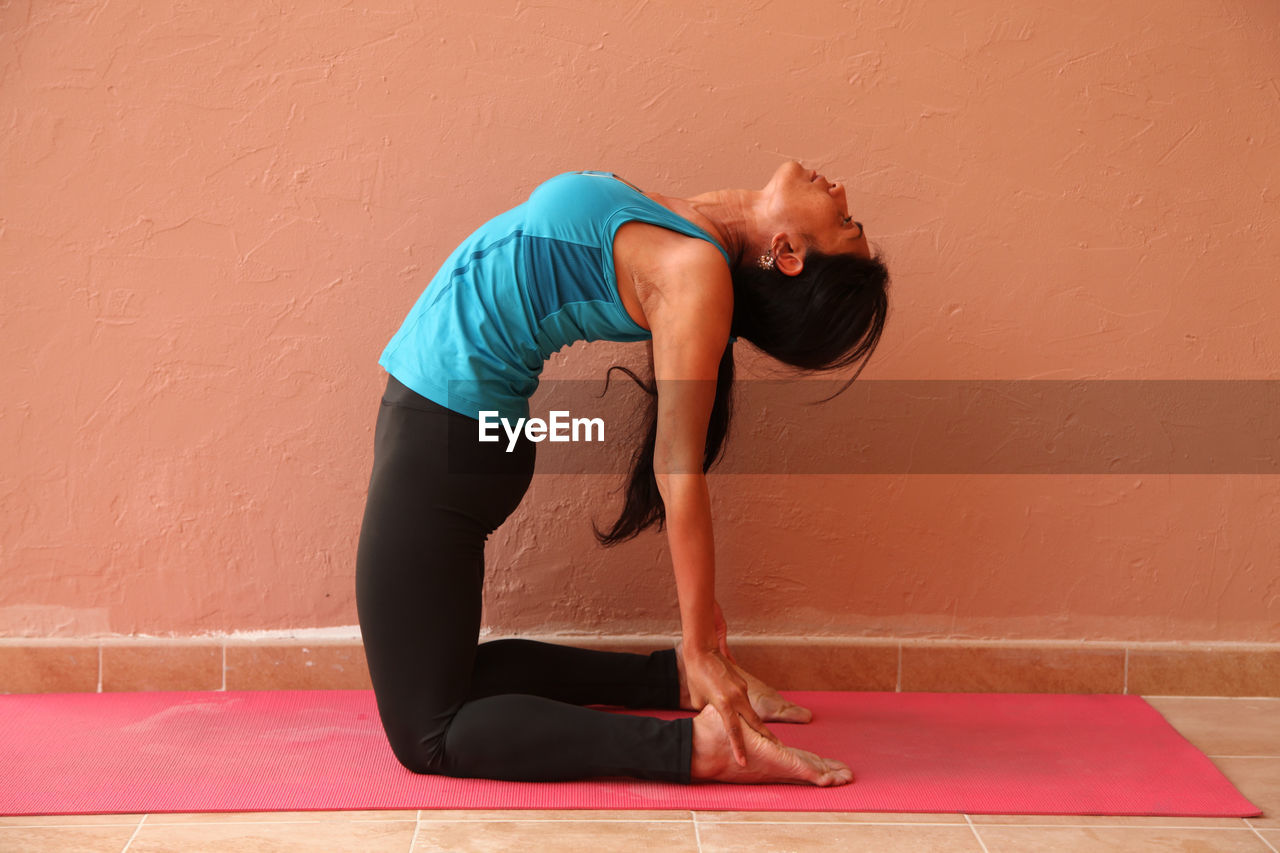 Young Woman Bending Over Backwards By Wall