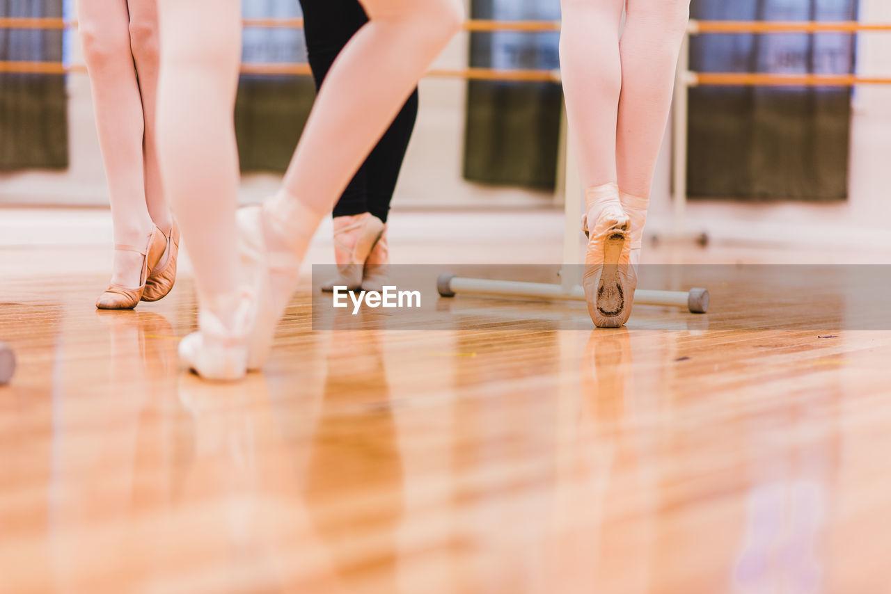 Low Section Of Ballet Dancers Dancing On Hardwood Floor