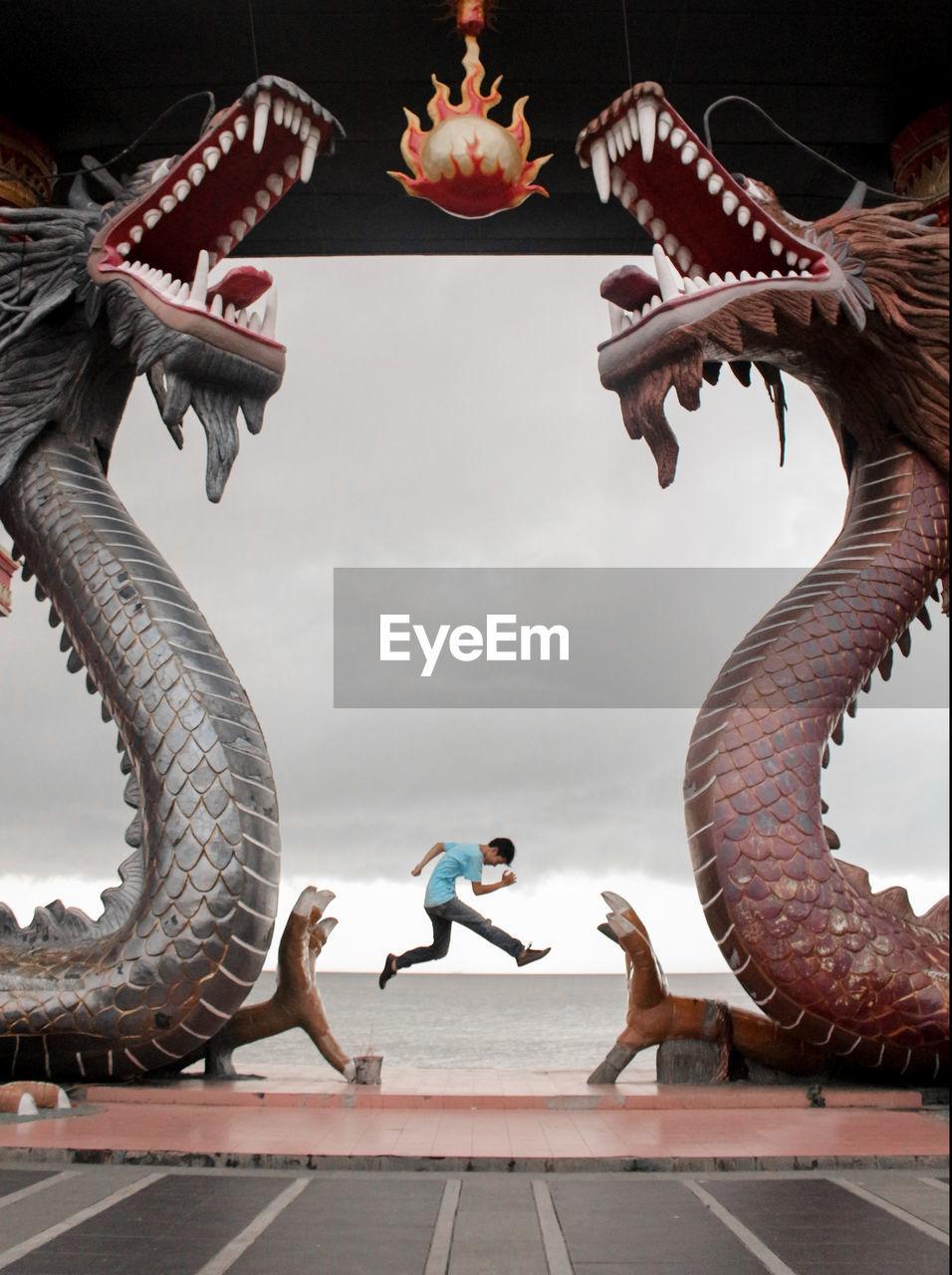Man Jumping At Beach Seen Through Dragon Statues Against Sky