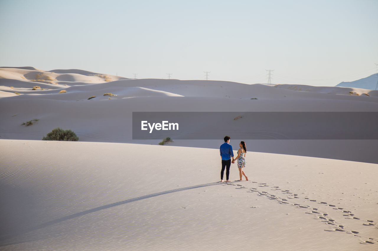 High angle view of couple walking on sand at desert