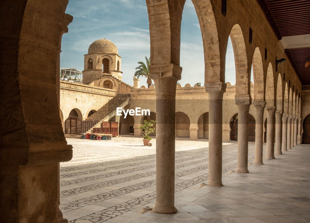 architecture, built structure, arch, architectural column, the past, history, travel destinations, building exterior, tourism, day, travel, arcade, building, nature, incidental people, ancient, city, old, place of worship, outdoors, ancient civilization, colonnade, courtyard