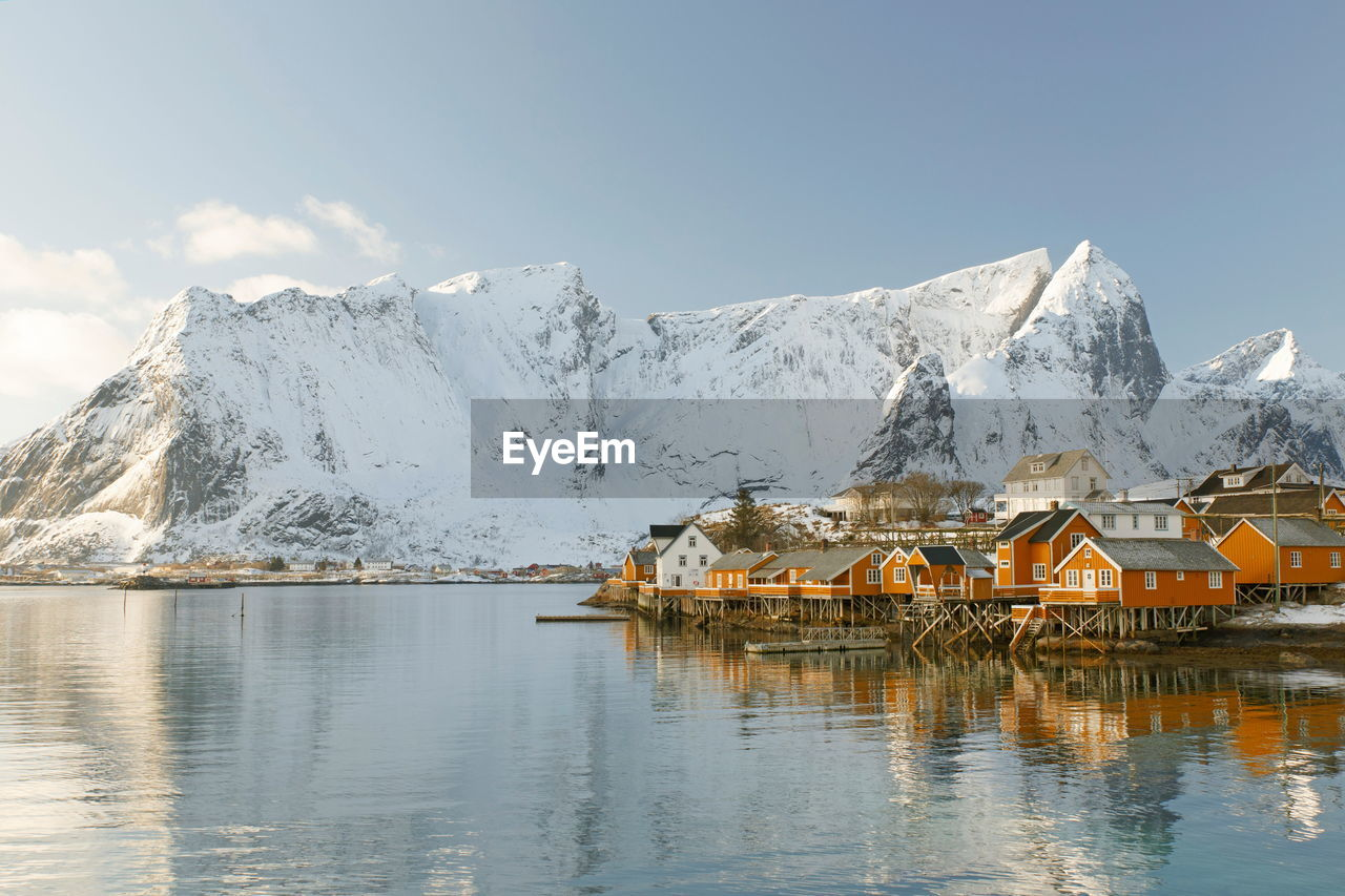 mountain, cold temperature, water, winter, sky, beauty in nature, scenics - nature, snow, building, architecture, built structure, house, waterfront, nature, building exterior, reflection, snowcapped mountain, tranquil scene, mountain range, no people, outdoors
