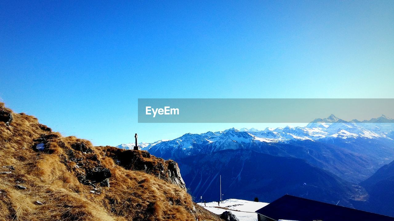 mountain, blue, clear sky, nature, snow, copy space, winter, cold temperature, beauty in nature, scenics, day, tranquil scene, mountain range, outdoors, tranquility, no people, landscape, adventure, building exterior, architecture, sky